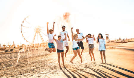 Happy friends group having fun at ferris wheel seaside - Summer vacations friendship concept with millenial guys and girls cheering at public beach - Warm sunset color tone with contrast filtered look Фото со стока - 151317655