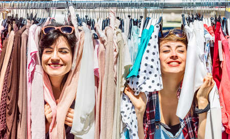 Happy women at weekly flea market - Female friends having fun together shopping cloth on sunny day - Millenial lifestyle concept with girlfriends enjoying everyday life moments - Bright vivid filter
