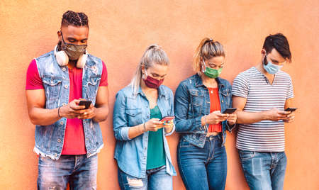 Multiracial friends with closed face masks using tracking app with mobile smartphones - Young milenial people sharing content on social media network - New normal lifestyle concept - Vivid filter Фото со стока - 151317915