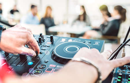 Closeup of dj playing on modern cd usb player at summer beach party - Happy hour and entertainment concept - Defocused background with shallow depth of field - Focus on mixing hand with bright filter