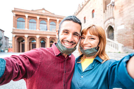 Happy boyfriend and girlfriend in love taking selfie with face masks at old town tour - Wanderlust life style travel concept with tourist couple on city sightseeing vacation - Bright warm filter