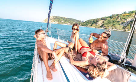Young millenial friends chilling on sailboat at sea trip - Guys and girls having summer fun together at sail boat party day - Luxury excursion concept on vivid filter with tilted horizon composition