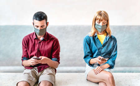 Bored addicted couple with protective masks using tracking app with mobile smartphones - Young millenial man and woman sharing content on social media - New normal lifestyle concept - Focus on faces