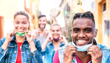 Multiracial friends with face mask after lockdown reopen - New normal friendship concept with guys and girls having fun together on travel vacation - Vivid filter with focus on afroamerican man smile Фото со стока - 151318117