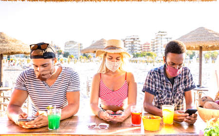 Multiracial friends with closed face masks using tracking app with mobile smartphones - Bored young milenial people at beach cocktail bar - New normal lifestyle concept - Warm vivid backlight filter
