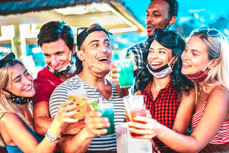 Happy multiethnic people drinking at night bar with open face masks - New normal summer concept with millenial friends having fun together - Focus on middle guy and girl with defocused background Фото со стока