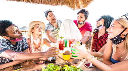 Young multiracial friends drinking at beach cocktail pub with open face mask - New normal summer concept with milenials having fun together toasting drinks - Bright filter with focus on central people Фото со стока - 151318123
