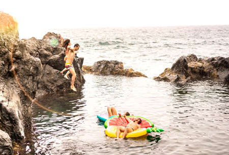 Crazy friends vacationers jumping on natural pool at travel beach location - Young people having fun diving in to wild sea - Wanderlust lifestyle concept on warm desaturated filter with sunshine halo Фото со стока