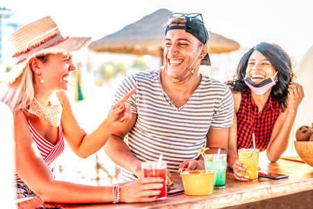 Friends trio drinking at beach cocktail bar wearing face masks - New normal summer concept with guy and girls having fun talking together at chiringuito stand - Warm backlight filter with focus on man