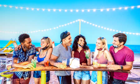 Happy multiracial friends drinking at beach cocktail bar wearing face masks - New normal summer concept with millennial people having fun together - High iso image with focus on middle guy and girl Фото со стока