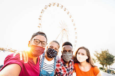 Multiracial milenial students taking selfie protected by face masks - New normal travel concept with young people having safe fun together at ferris wheel - Bright sunshine filter with tilted angle