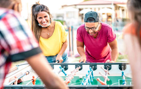 Multiracial friends play kicker table football at open space bar - New normal lifestyle concept with happy milenials having fun together with open face mask - Bright vivid filter with focus on guy Фото со стока - 152445627