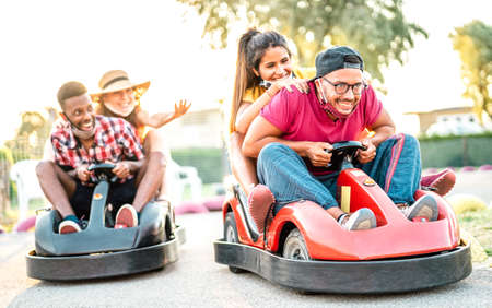 Milenial friends having fun at children playground on go kart race - Young people with face mask competing on mini car racing - New normal lifestyle concept with focus on right guy - Backlight filter Фото со стока
