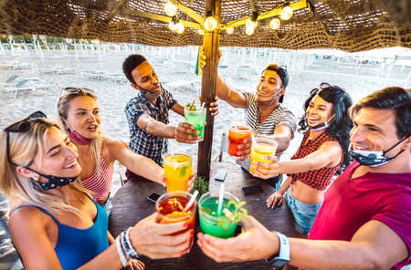 Young trendy friends toasting at beach cocktail bar chiringuito with face mask - New normal summer concept with people having fun together cheering drinks - Warm dark filter with focus on central guys