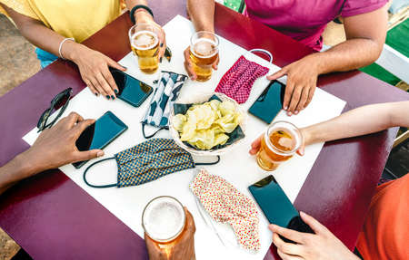 Close up of friends hands near face masks on table with mobile smart phones and beers - New normal lifestyle technology concept with people at party bar - Bright vivid filter on wide angle top view Фото со стока - 152810868