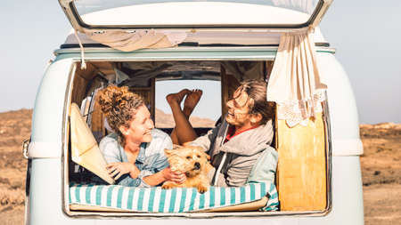 Hipster people with cute dog traveling together on vintage minivan - Wanderlust and life inspiration concept with hippie couple on mini van adventure trip - Bright warm filter Stock fotó