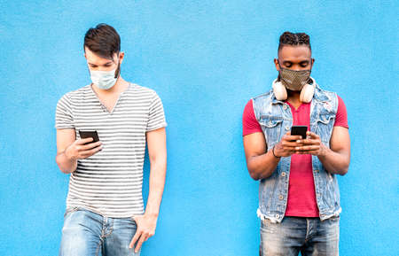 Multiracial male friends with face masks using tracking app with mobile smart phones - Young millenial people watching updates on social media networks - New normal lifestyle concept on bright filter