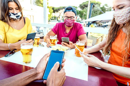 Milenial friends with closed face masks using tracking app with mobile smartphones - New normal lifestyle concept by bored young people at brewery bar - Bright vivid filter with focus on lower phone