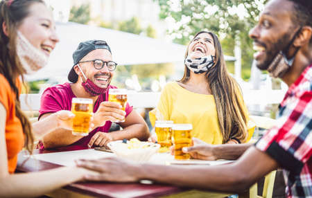 Young people drinking beer with open face masks - New normal lifestyle concept with friend having fun together talking on happy hour at brewery bar - Bright vivid filter with focus on left guy