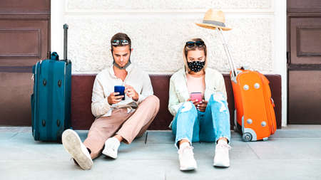 Young couple with face mask using mobile smart phones - Young people checking online reservations sitting on floor outside train station - New normal travel and lifestyle concept - Warm bright filter