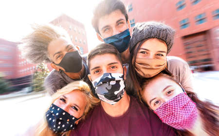 Multiracial friends taking selfie with face masks - Happy friendship concept with young students having fun together after university reopening - Bright marsala filter with radial defocusing