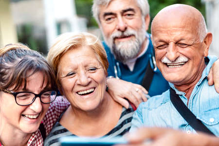 Happy senior friends taking selfie around old town street - Retired people having fun together with mobile phone - Positive elderly lifestyle concept with focus on blond woman