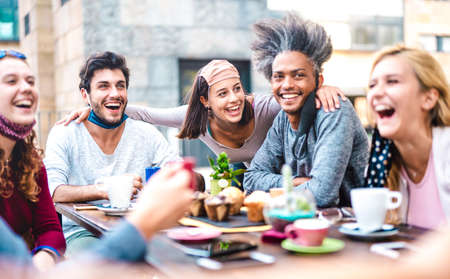 Multiracial friends having fun drinking together at coffee house - Young people laughing at restaurant cafeteria - New normal lifestyle concept with happy guys and girls at cafe bar - Bright filter