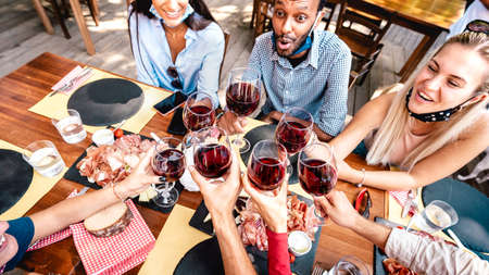 Friends drinking red wine at restaurant bar wearing open face mask - New normal lifestyle concept with happy people having fun together toasting at tavern bar - Warm vivid filter with focus on glasses