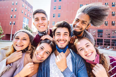 Multiracial friends taking selfie with opened face mask at college campus - Happy friendship concept with young students having fun together after university reopening - Bright backlight filter