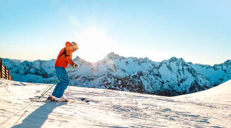 Professional skier athlete skiing at sunset on top of french alps - Winter vacation and sport concept with adventure guy on mountain ski resort riding down the slope - Bright sunshine filter 版權商用圖片
