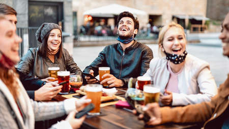 Young friends drinking beer wearing face mask - New normal lifestyle concept with people having fun together talking on happy hour at outside brewery bar - Bright warm filter with focus on central guy