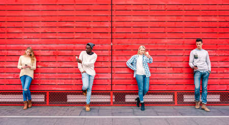 Multicultural friends group using smartphone by red wooden background - Technology and urban lifestyle concept with millenial people sharing content online with modern mobile phones - Vivid filter