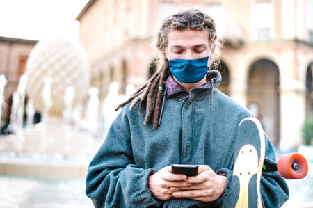 Unhappy guy with protective mask using tracking app on mobile smartphone - Young worried millenial sharing content on social media - New normal lifestyle concept - Bright filter with focus on face