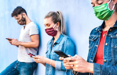 Milenial friends using mobile phone covered by face mask - Young people sharing content on cellphone - New normal concept about always connected teenager - Vivid azure filter with focus on right hands Фото со стока