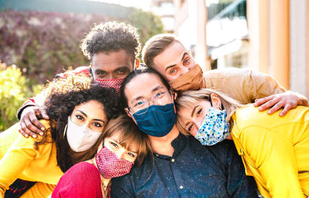 Multicultural milenial friends taking selfie smiling behind face masks - New normal friendship and life style concept with young people having fun together outside - Warm bright vivid filter Фото со стока