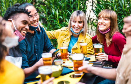 Multiracial people drinking beer with opened face mask - New normal friendship concept with friends having fun together on happy hour at brewery garden party - Vivid filter with focus on yellow jacket Фото со стока