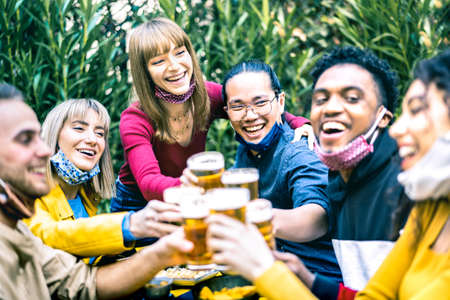 Young people toasting beer with opened face masks - New normal life style concept with happy friends having fun together drinking at brewery bar garden - Bright contrast filter with focus on asian guy