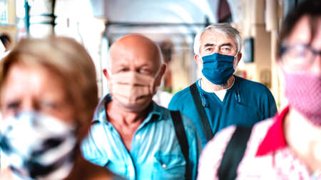 Urban crowd of adult citizens walking on city street during pandemic - New reality life style concept with senior people with covered faces - Selective focus on bearded man with blue protective mask