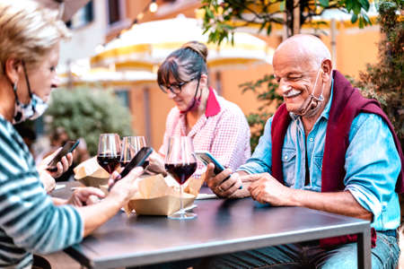 Mature people using mobile smart phone with open face mask - Senior retired adults watching positive news on smartphone - New normal lifestyle concept at restaurant wine bar - Vivid contrast filter Фото со стока