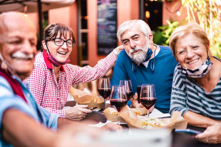 Happy senior friends taking selfie at restaurant with open face mask - Retired people having fun together at winebar after lockdown reopening - Positive elderly life style concept on vivid warm filter Фото со стока