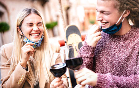 Young couple in love wearing open face masks and having fun at winery bar outdoors - Happy hipster lovers toasting wine at restaurant patio - New normal relationship concept on bright pastel filter Фото со стока
