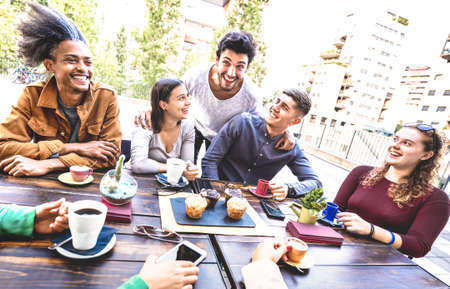 People group drinking cappuccino at coffee bar restaurant - Friends talking and having fun together at outdoors cafeteria - Life style concept with happy men and women at cafe - Warm bright filter