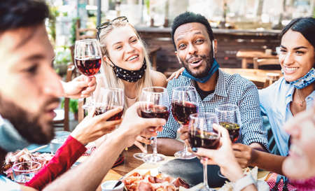 Multiracial people toasting wine at restaurant garden wearing open face mask - New normal lifestyle concept about happy friends having fun together - Bright filter with focus on guy looking at camera Фото со стока