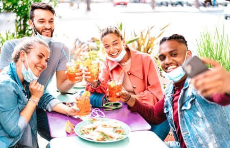 Multicultural people taking selfie with open face masks at cocktail bar - New normal life style concept with young friends having fun toasting together at restaurant garden party - Bright warm filter