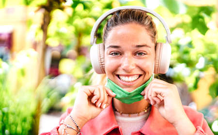 Young woman smiling looking at camera with open facial mask and headphones - New normal lifestyle concept with millenial girl having fun outdoors after lockdown reopening - Warm bright filter
