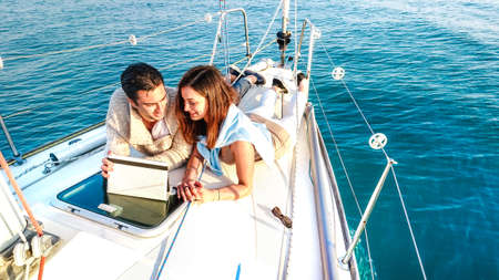 Young couple in love having fun with tablet pc on sailboat Banque d'images
