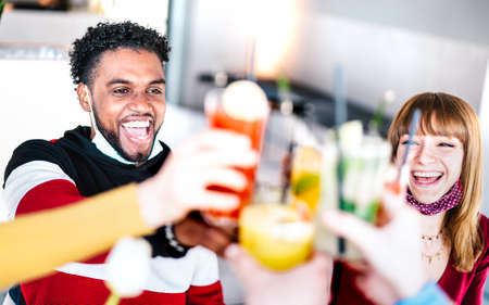 Young friends drinking at cocktail bar wearing open face mask