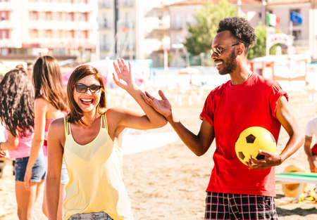 Multiracial couple ready to play beach soccer on sunny day - Summer vacation concept and multi cultural friendship with guy and girl having fun together - Bright warm filter with focus on right man