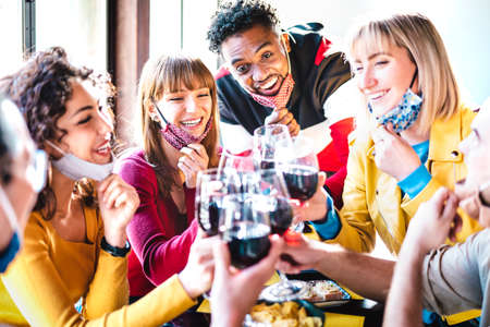 Multiracial friends toasting red wine at restaurant bar wearing open face mask
