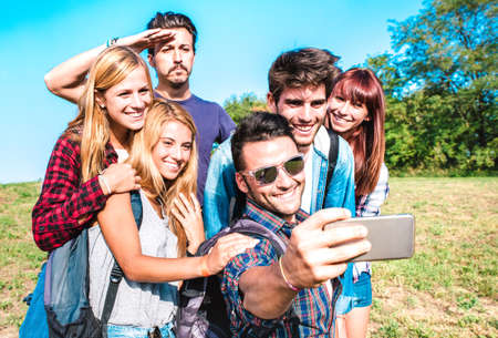 People group taking selfie at trekking excursion - Happy friendship and freedom concept with young millenial friends having fun together at camping experience - Bright vivid filter